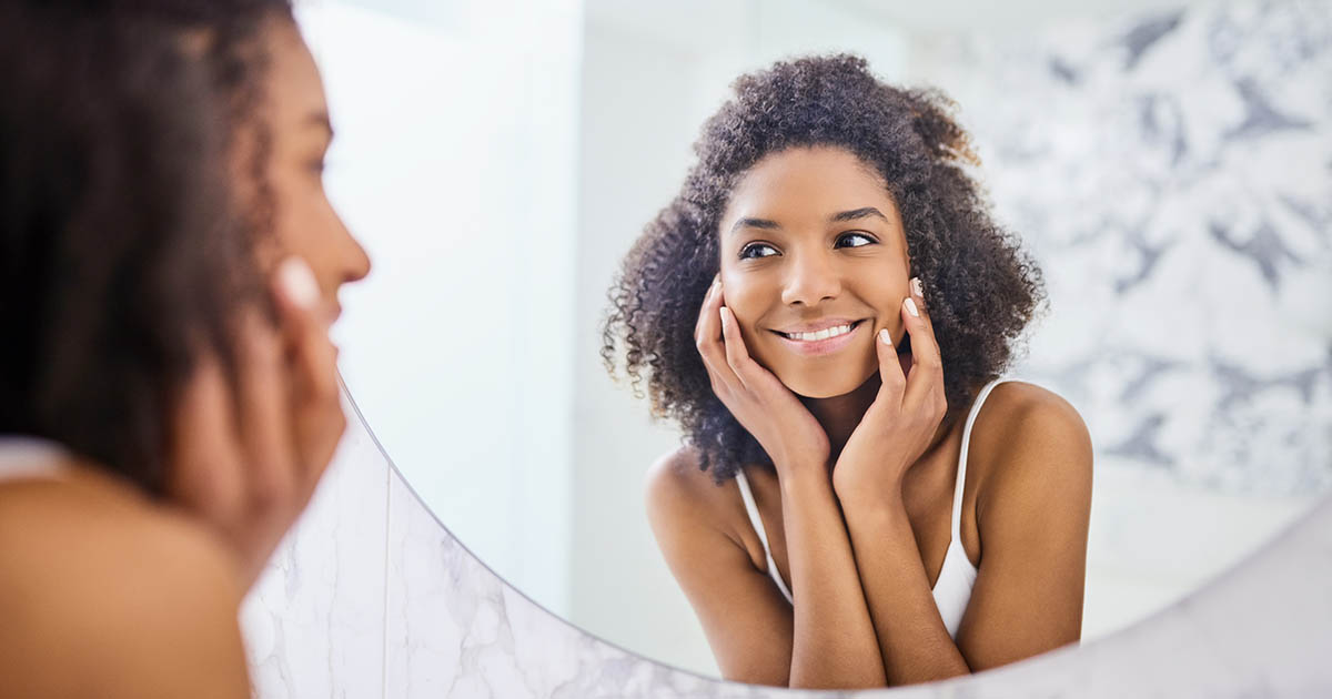 Young woman admiring her face in the bathroom mirror