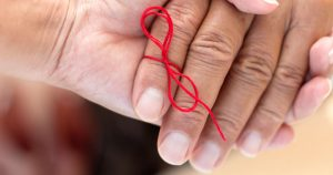 Red ribbon tied around a finger