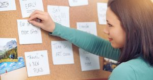 Young woman pinning notes on a corkboard at home