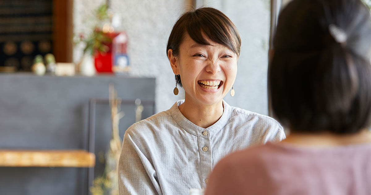 Two friends at a cafe, laughing and talking