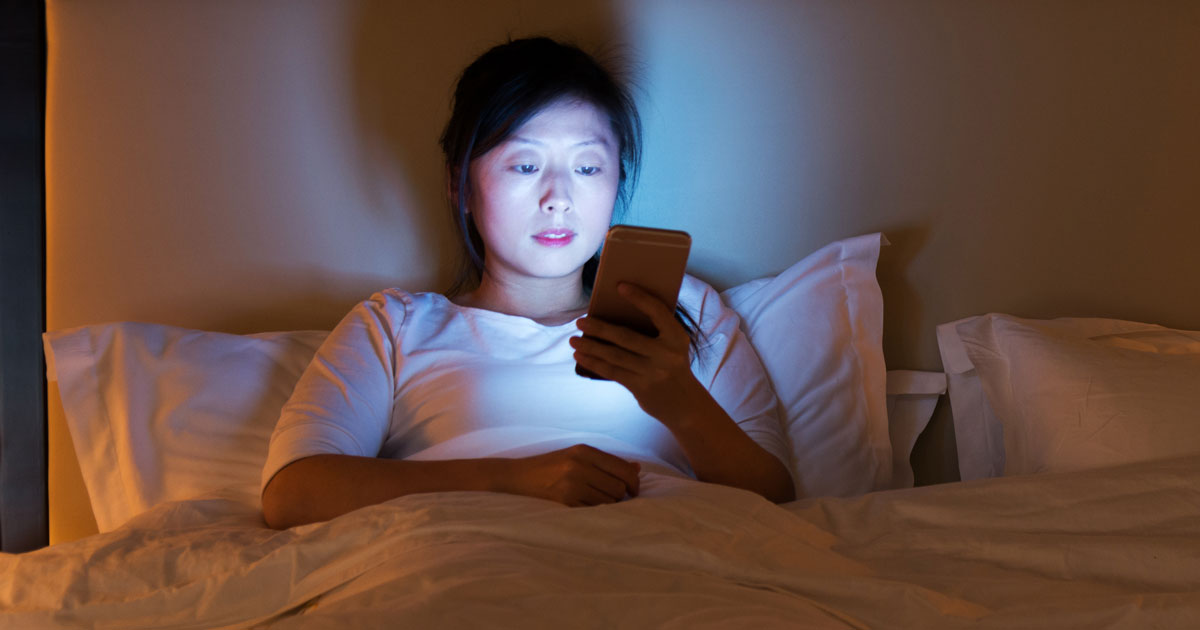Woman is on her phone, while lying in bed