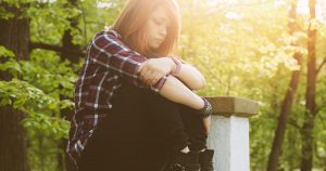 Depressed teen sitting outside