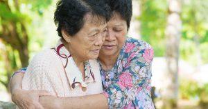 Family caregiver hugging upset patient