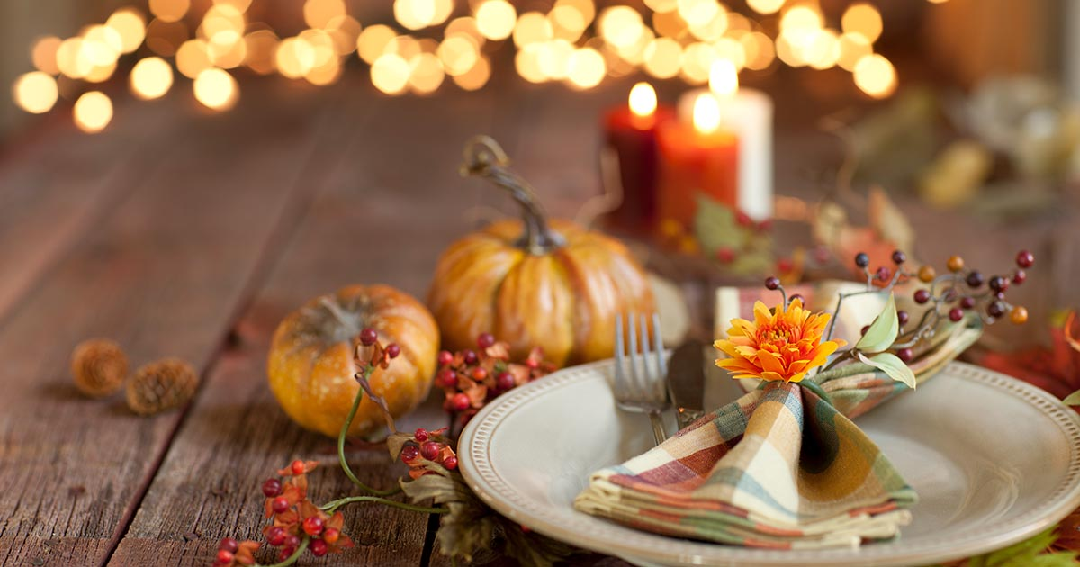 Thanksgiving dining table place setting on an old wood rustic table