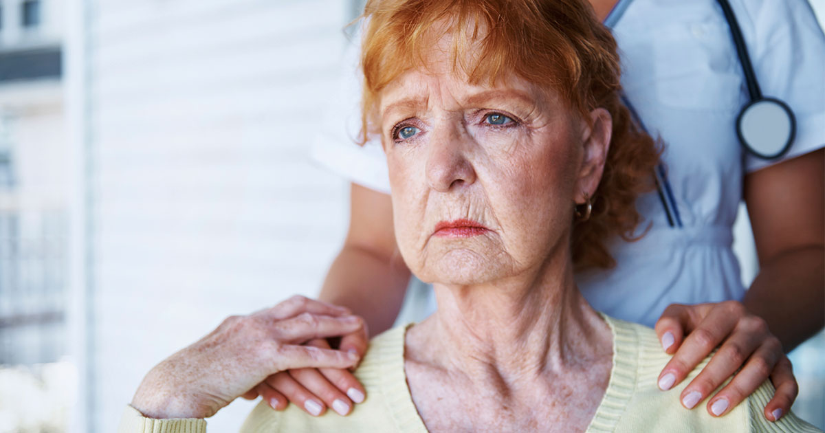 Anxious senior woman is comforted by caregiver
