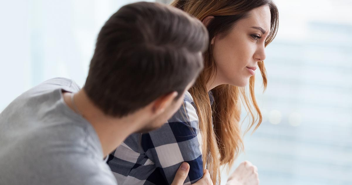 Caring man comforting upset wife after fight