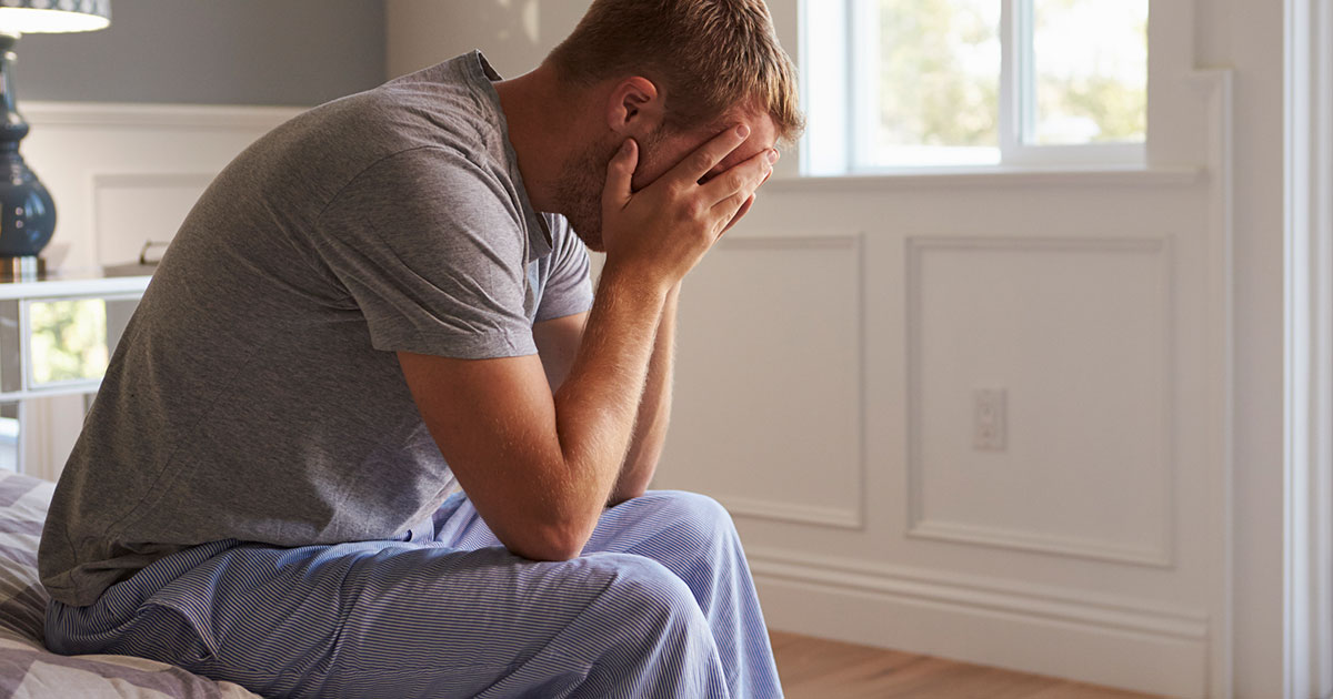Depressed man sitting at the edge of his bed