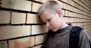 Depressed child leaning his head against a brick wall