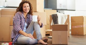 Woman sitting on the floor with a drink in hand, surrounded by moving boxes