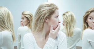 Woman surrounded by multiple mirrors, looking at her own reflection