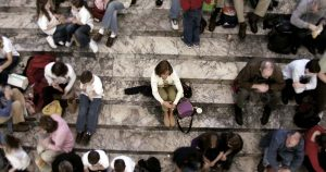 Person sitting alone on stair steps with crowd circled around them