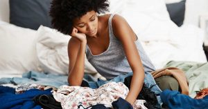 Sad woman sitting among a pile of clothes
