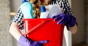 Woman holding a bucket of cleaning supplies