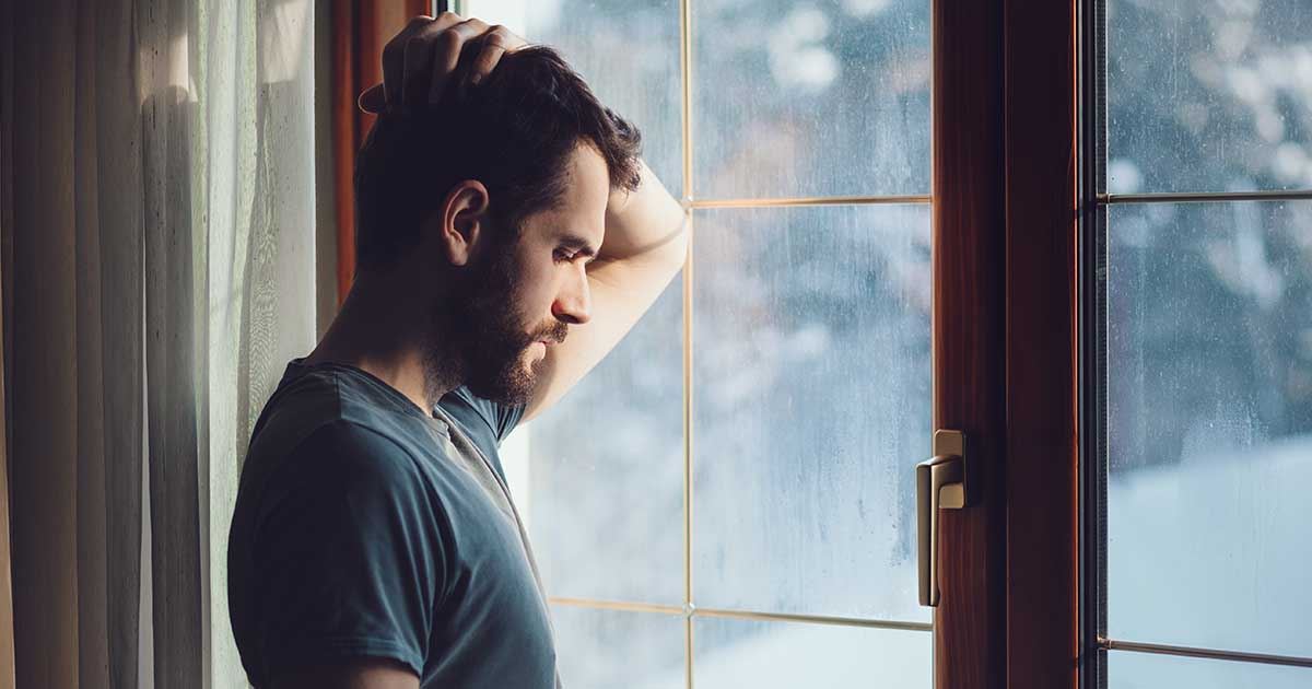 A man, living alone, is looking out a window