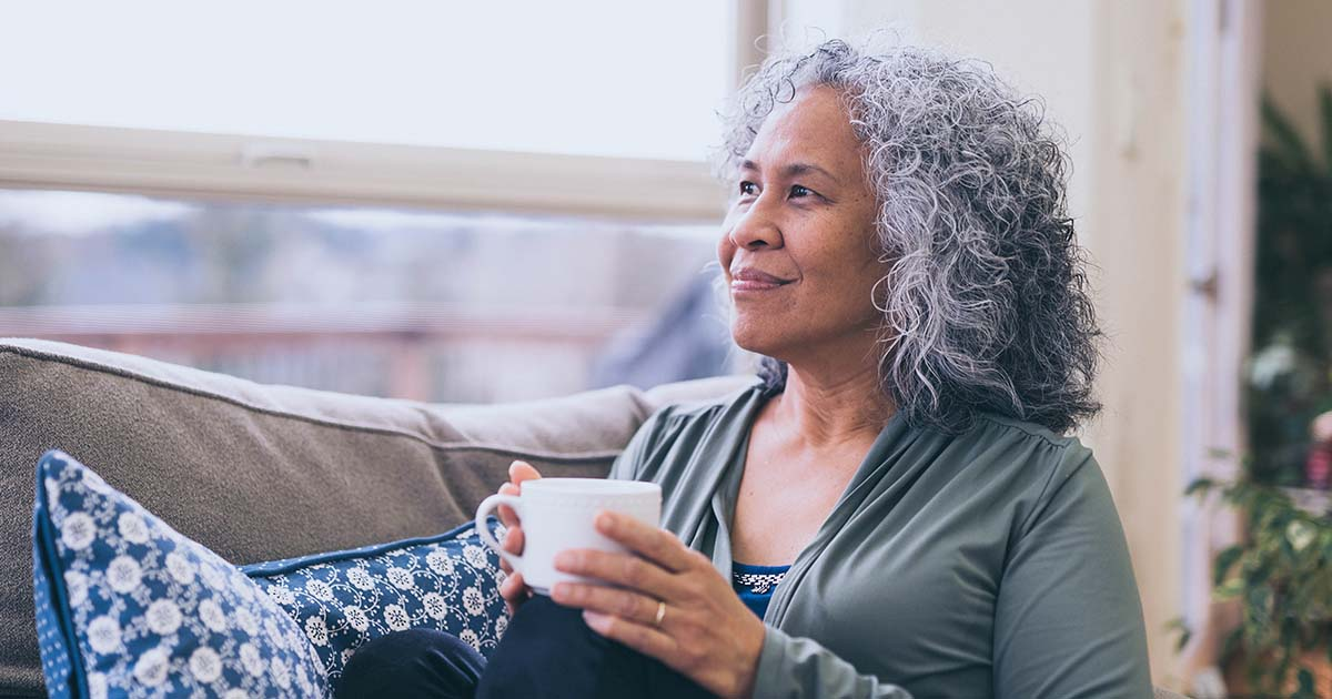 Smiling woman sitting on sofa and drinking a cup of coffee while looking out a window