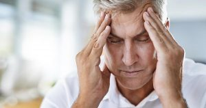 Mature businessman suffering with a headache at work