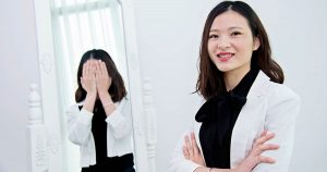 A smiling woman is standing in front of a mirror, her reflection is showing her crying