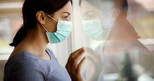 a woman wearing a face mask looking sadly out the window. experiencing feelings of depression during quarantine